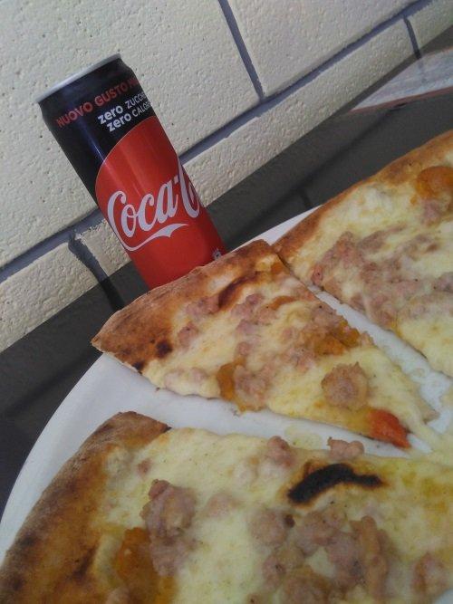 un piatto di pizza e accanto una lattina di coca cola