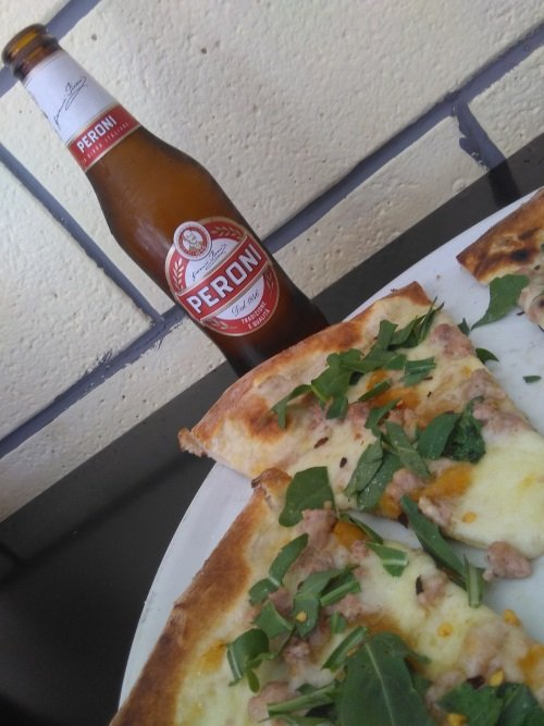 una pizza e accanto una bottiglia di birra Peroni