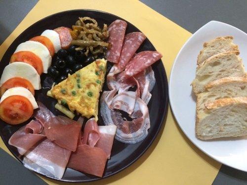 un piatto di salumi, formaggi e delle olive