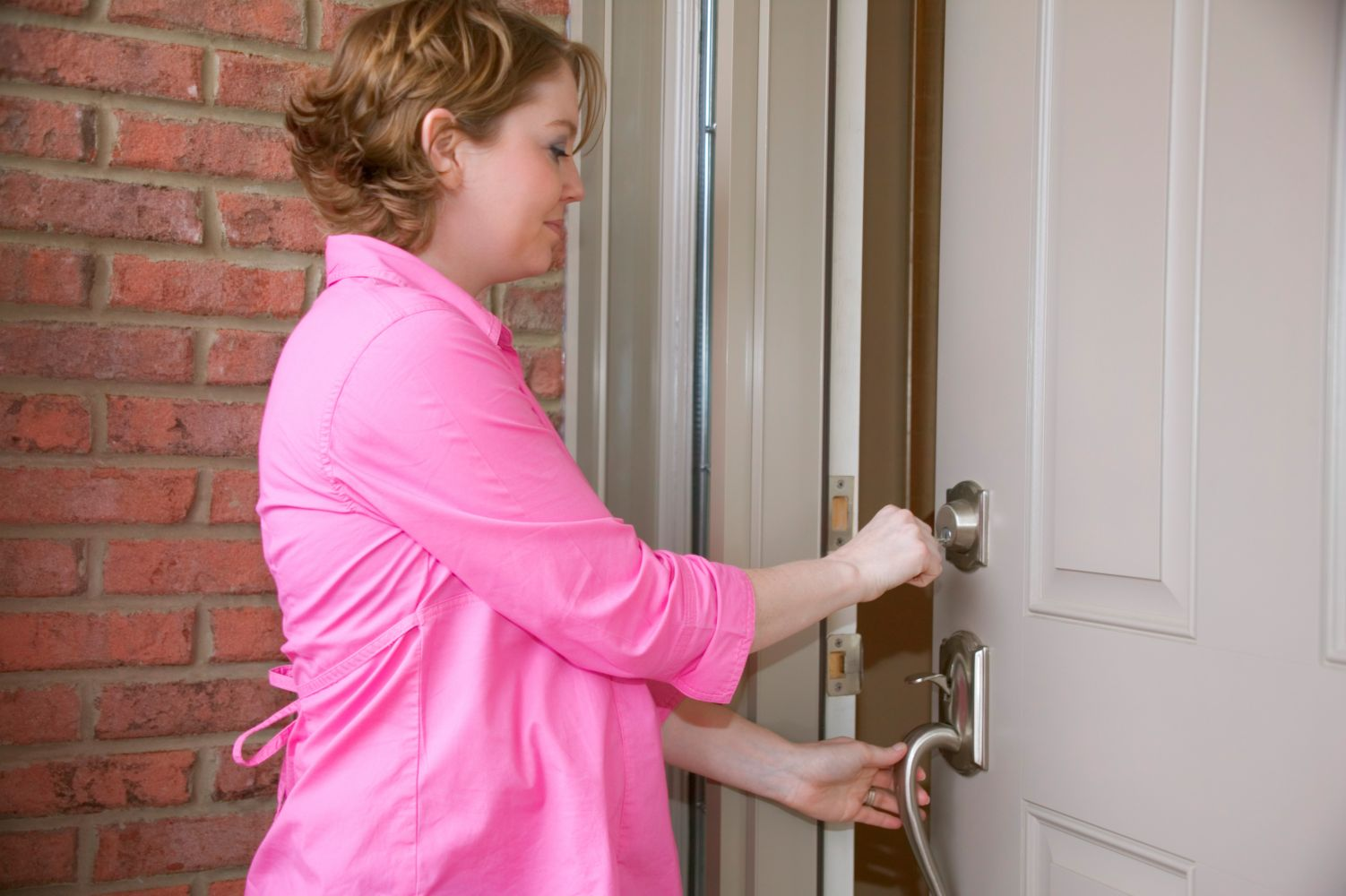 Woman opening lock provided by locksmithing experts in Anchorage, AK