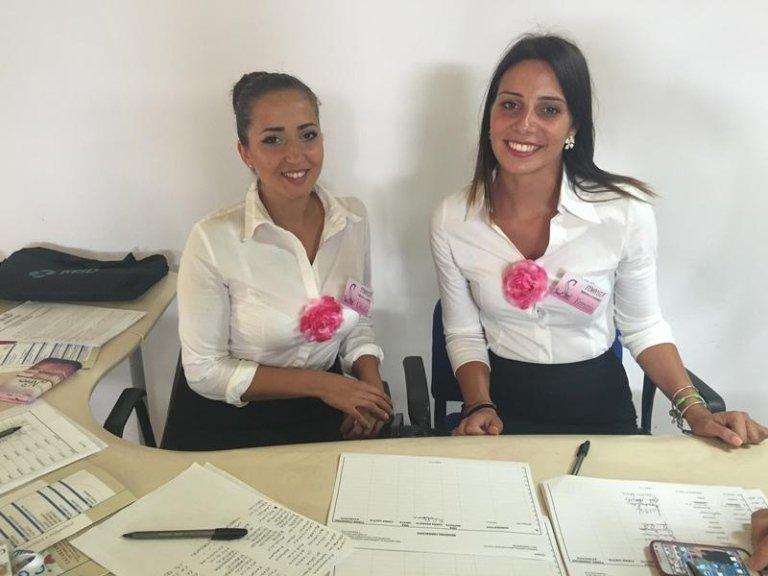 due ragazze con camicia bianca e gonna di color nero sedute alla scrivania