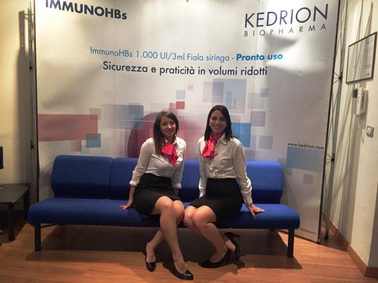 due hostess sedute sulle sedie e dietro un cartello