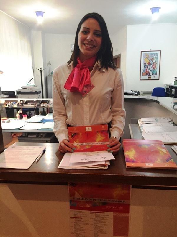 una hostess in un ufficio in piedi dietro a un bancone