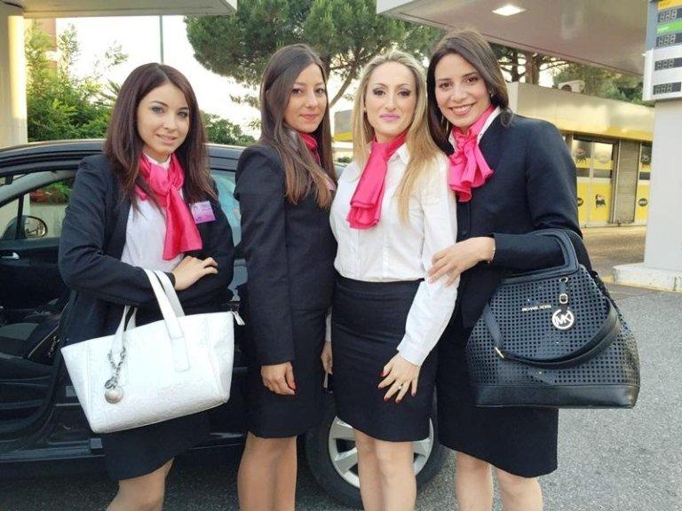 quattro hostess in piedi davanti ad una macchina