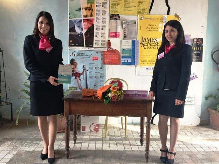 Due hostess davanti a un tavolo con un bouquet di fiori e dei poster sul muro