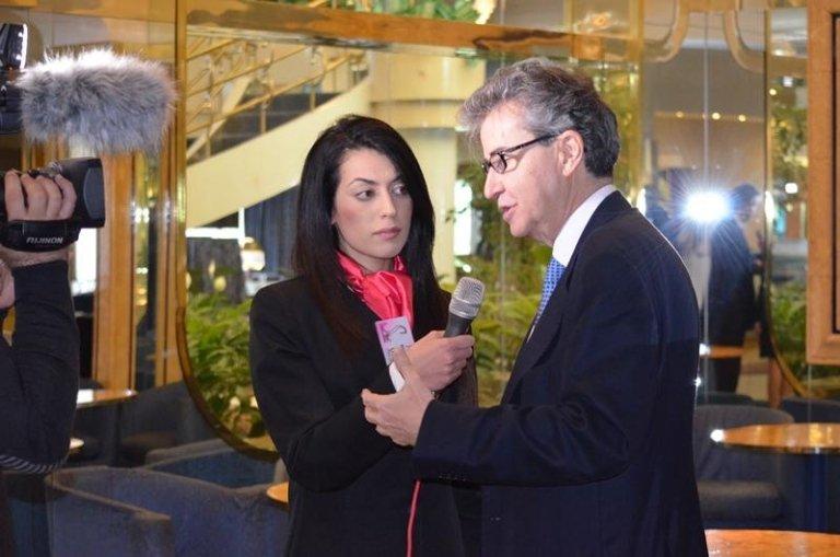 una hostess che tiene il microfono mentre un uomo parla in un'intervista