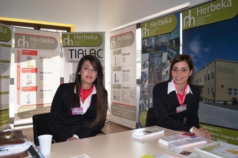 due hostess sedute davanti a un tavolo con delle brochure