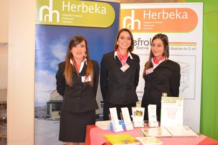 tre hostess in piedi davanti a dei cartelli con scritto Herbeka