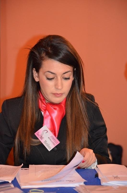 una hostess seduta al tavolo ementre controlla dei documenti