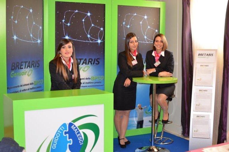 tre hostess davanti a dei cartelli con scritto Bretaris