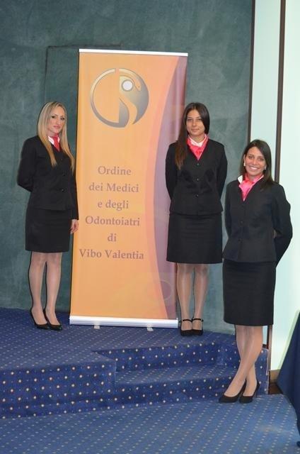 tre hostess davanti a dei cartelli con scritto Ordine dei Medici