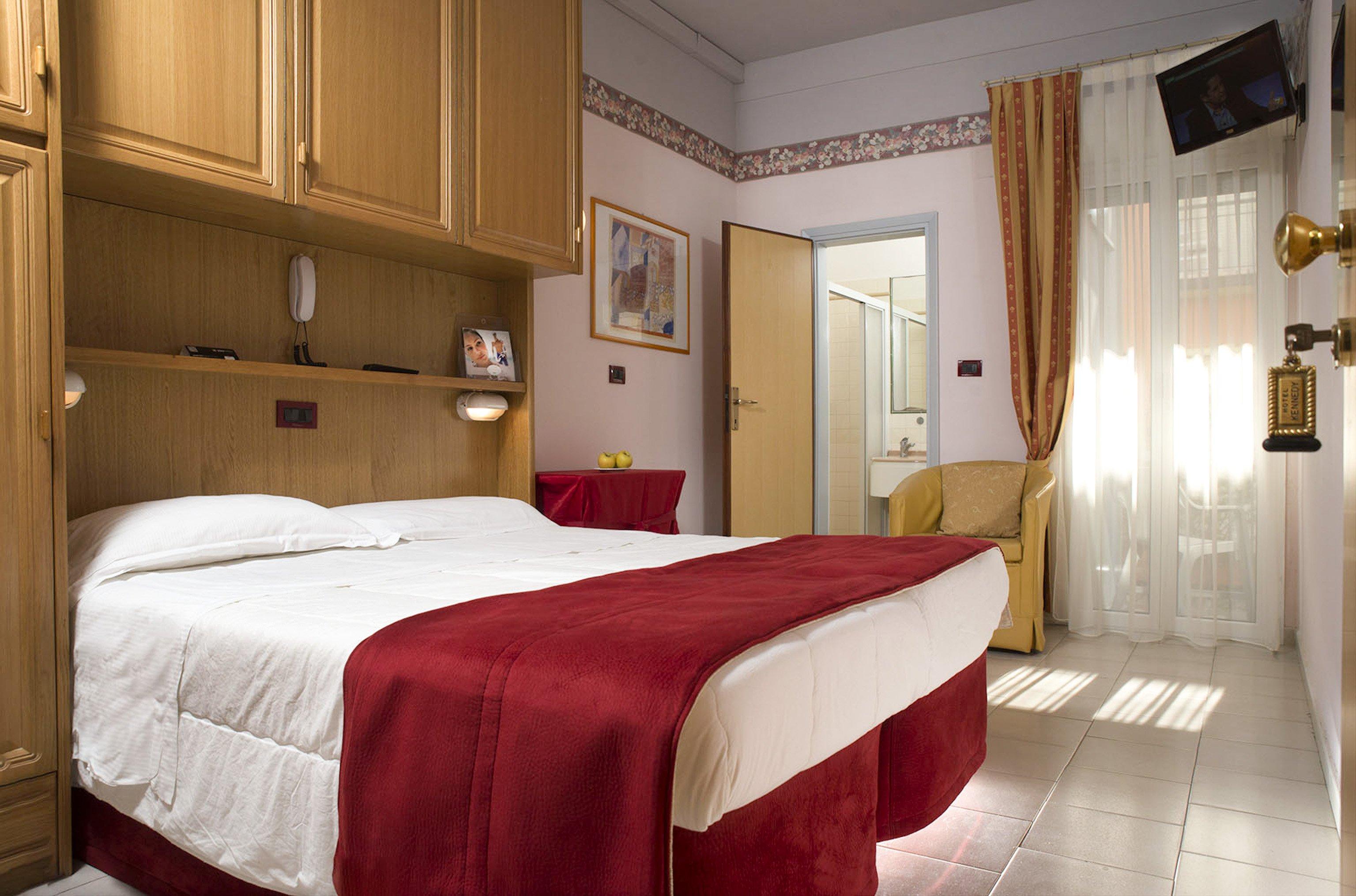 camera matrimoniale con lenzuola bianche e copriletto rosso