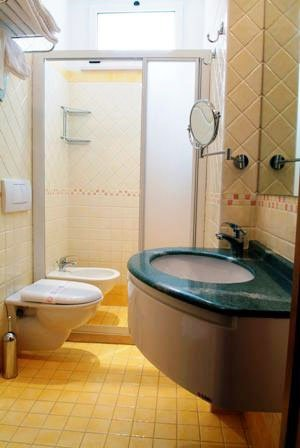 un bagno con box doccia e lavabo verde