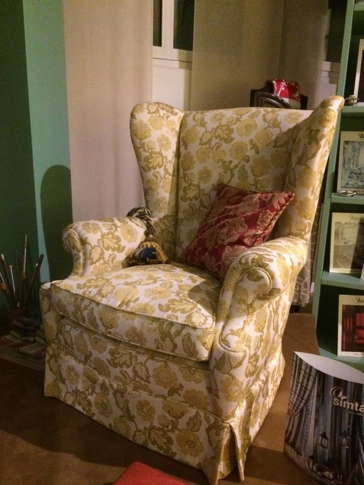 una poltrona bianca a fiori gialli e un cuscino rosso