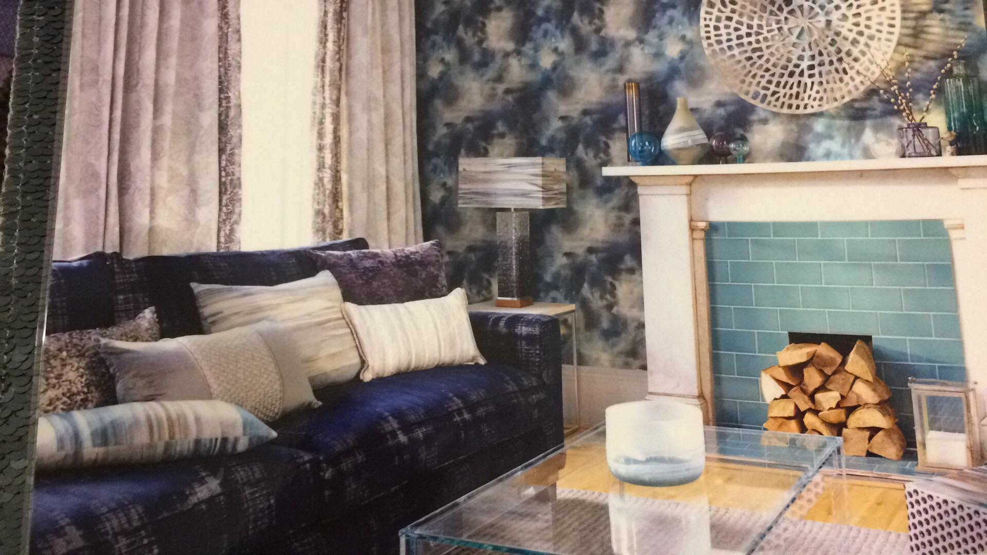 un divano viola,dei cuscini e una lampada dorata da terra