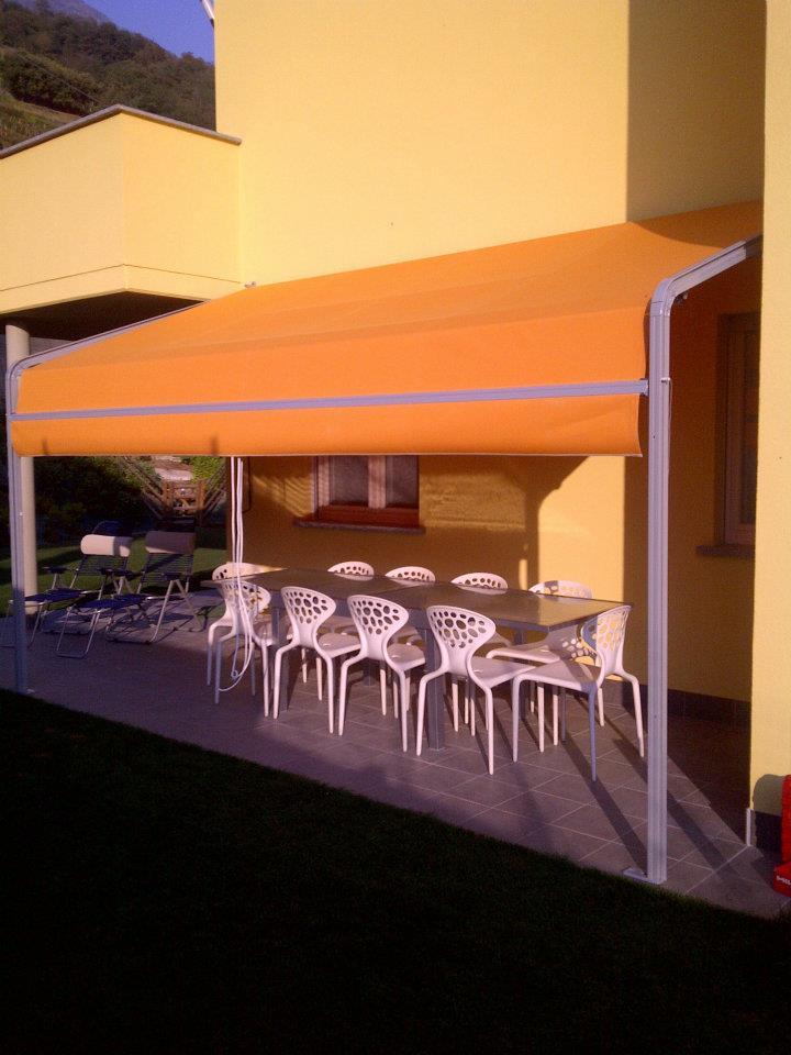 un tendone arancione e sotto un tavolo con delle sedie bianche