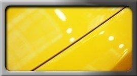 dettaglio di auto gialla, parte di cofano, parte di parafango