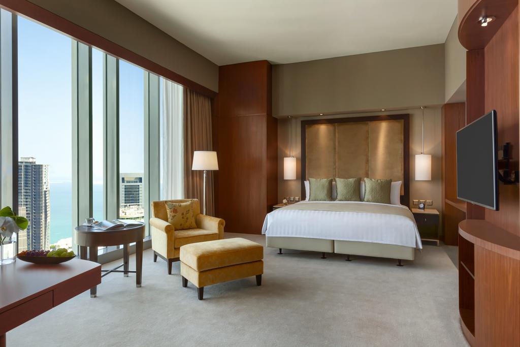 camera d'Hotel con letto matrimoniale e poltrona gialla