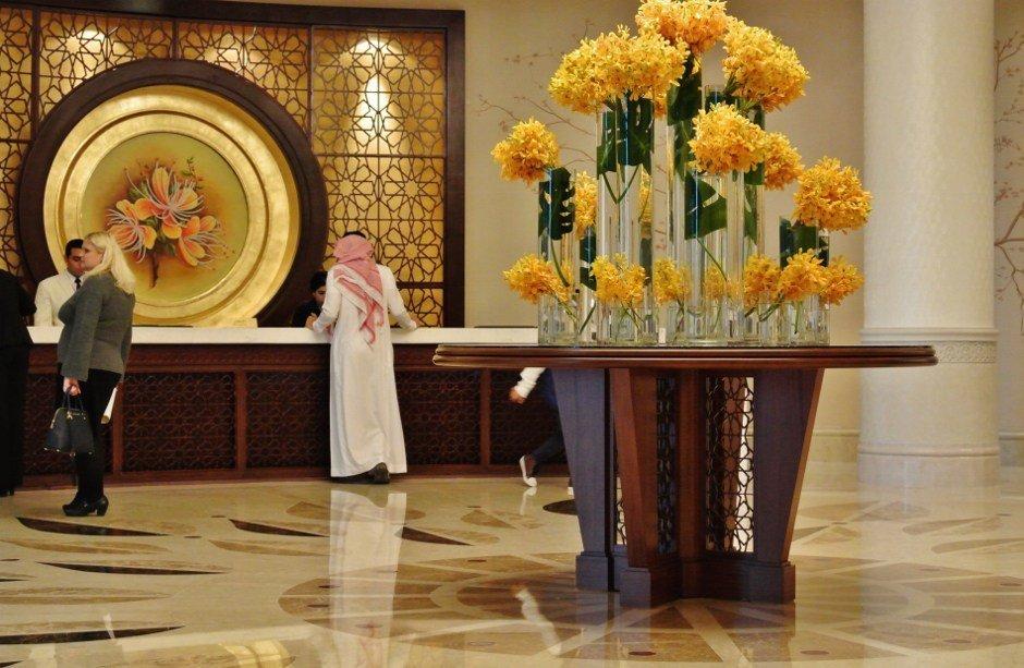 hall con grande vaso con fiori gialli e clienti alla reception