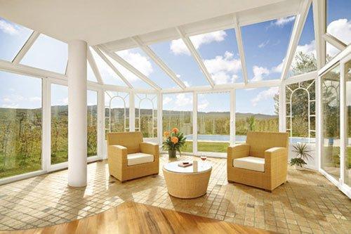 poltrone con tavolino da te sotto veranda di vetro trasparente