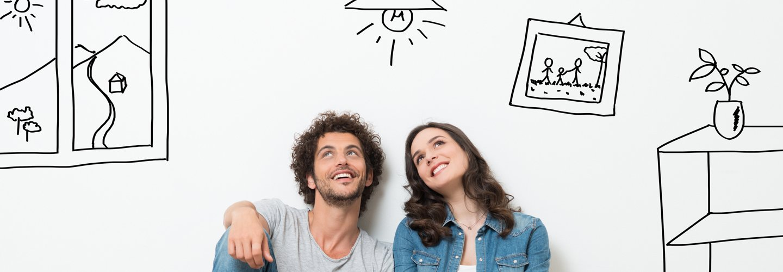 Una giovane coppia seduta con la schiena poggiata su una parete bianca con disegni stilizzati