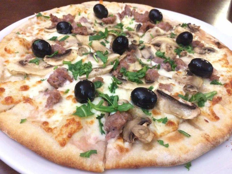 Pizza bianca di funghi e bacon con rucola
