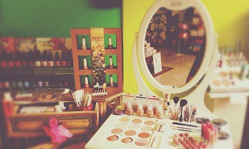 Uno specchio con dei cosmetici davanti e sulla destra un altro mobile con degli smalti di vari colori