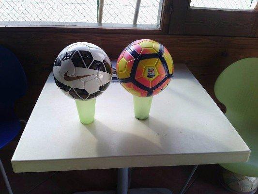 Due palle da futbol su due bicchieri di plastica
