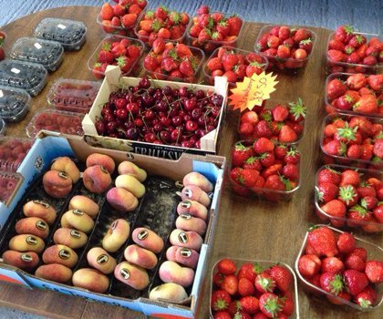 Baskets and punnets of strawberries, flat peaches, cherries, blueberries and raspberries