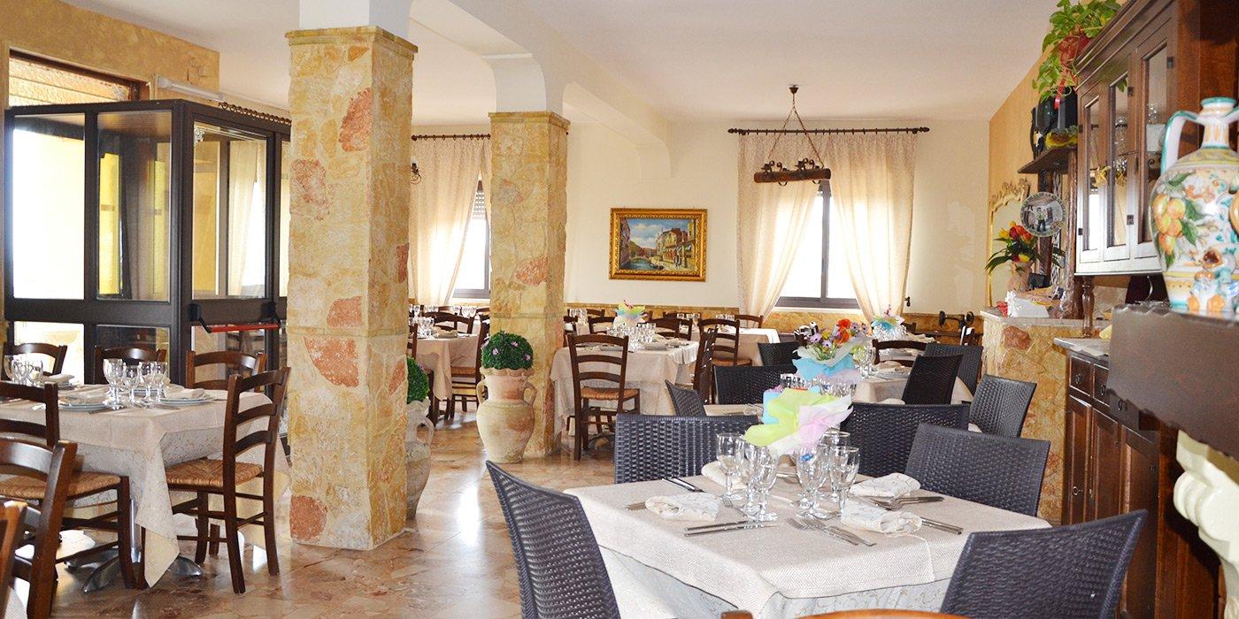 interno del ristorante, atmosfera luminosa con colonne vasi di fiori e tavoli apparecchiati