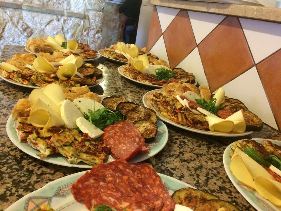 piatti di salumi, frittate alle verdure, formaggi, rucola e melanzane su un piano di lavoro in granito