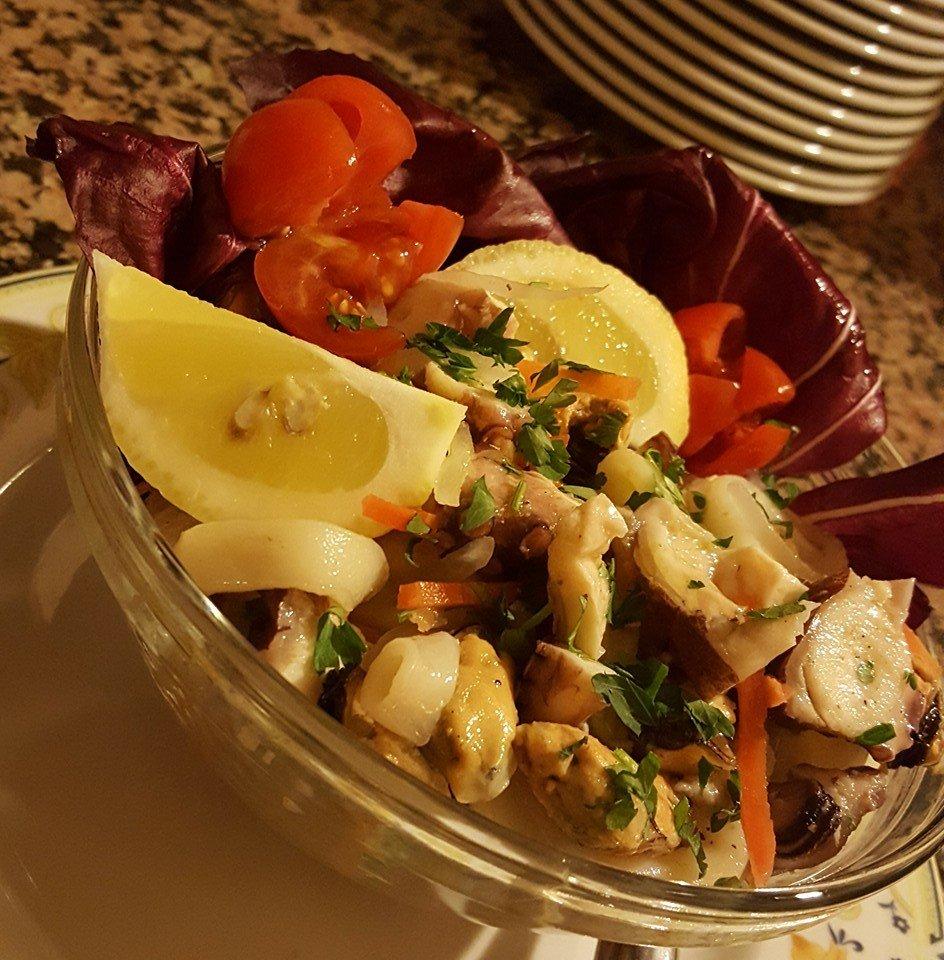 insalata di mare con pomodori,radicchio rosso, limoni all'interno di un insalatiera di cristallo