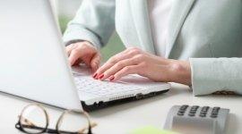 mani di una donna, computer portatile su scrivania, occhiali da vista e calcolatrice