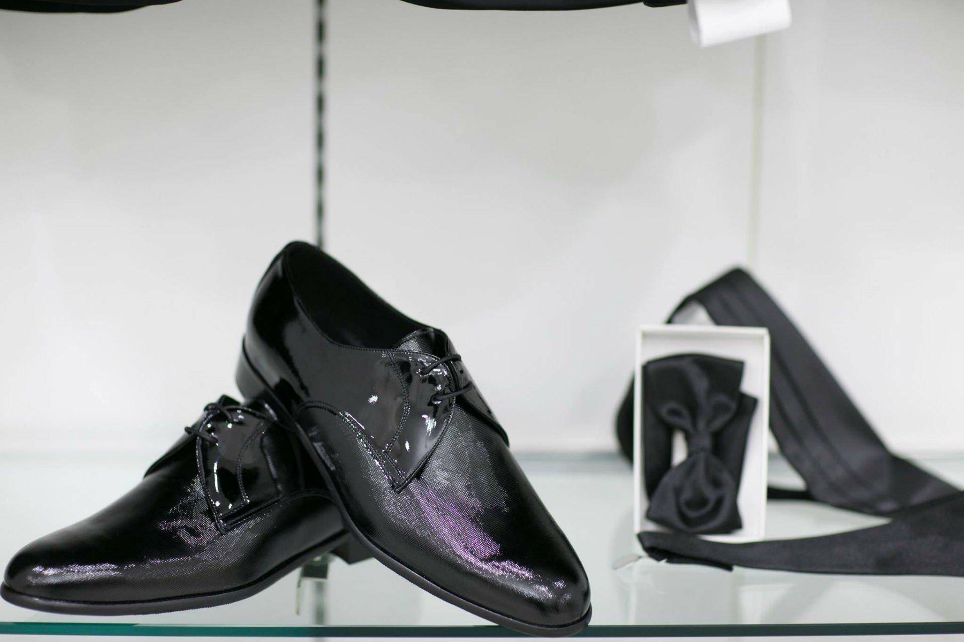 delle scarpe nere classiche, un papillon e una cravatta