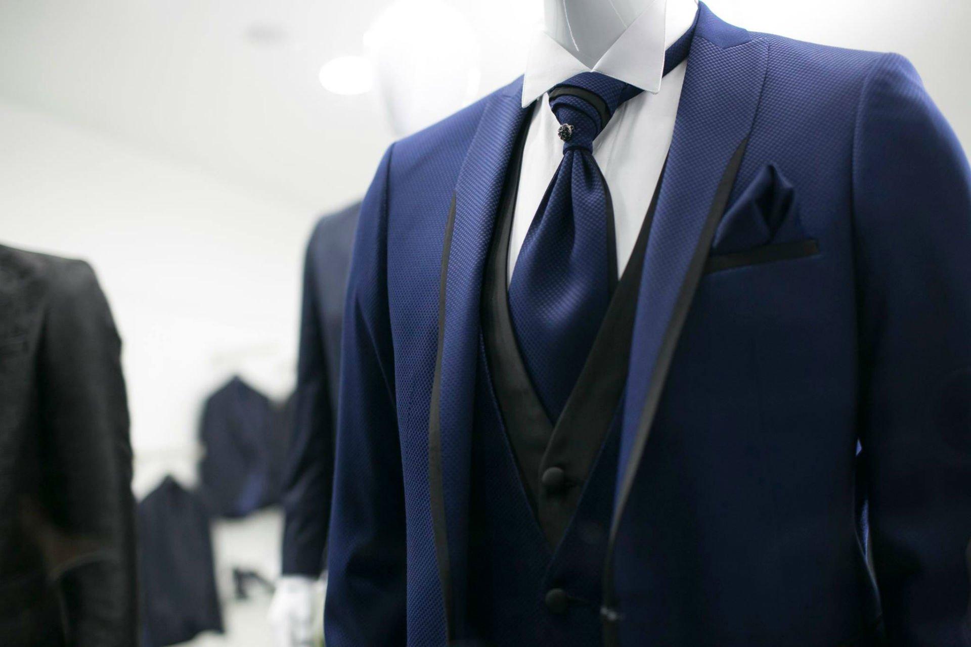 un completo blu con cravatta blu e camicia bianca