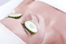 woman with slices of cucumber on her eyelids