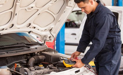 a mechanic carrying out engine diagnostics of a car