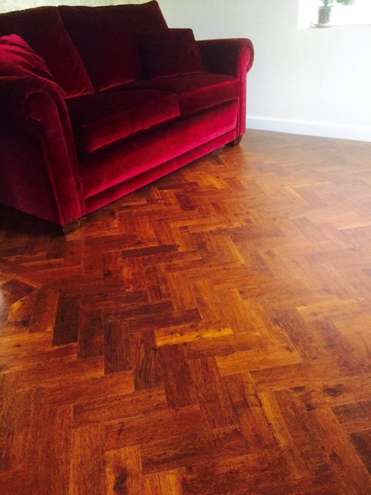 Red velvet sofa on parquet flooring