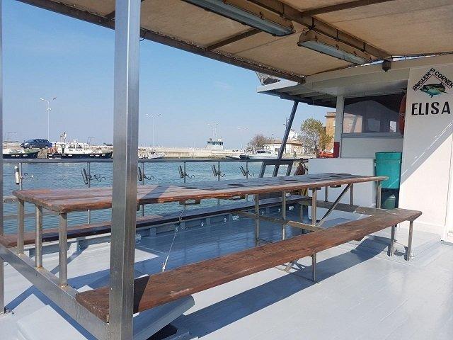 un tavolo di legno e delle panchine all'esterno di una motobarca