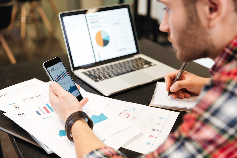 Analista crea un grafico al pc aiutandosi con uno smartphone e dei documenti