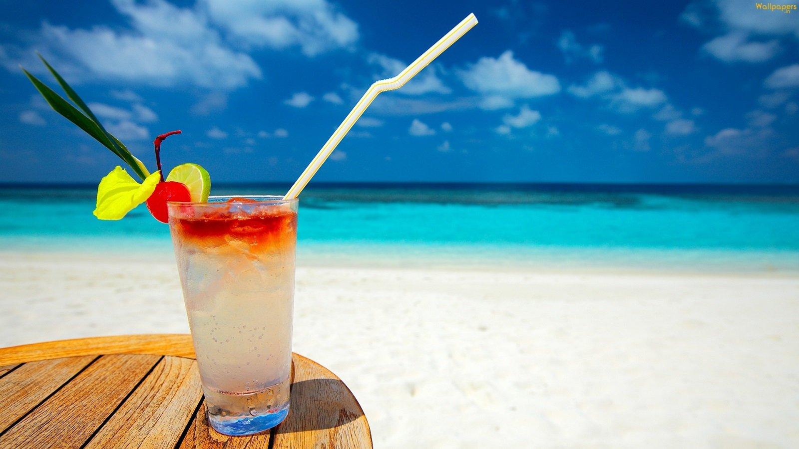 paesaggio di mare con primo piano di drink in un bicchiere con cannuccia