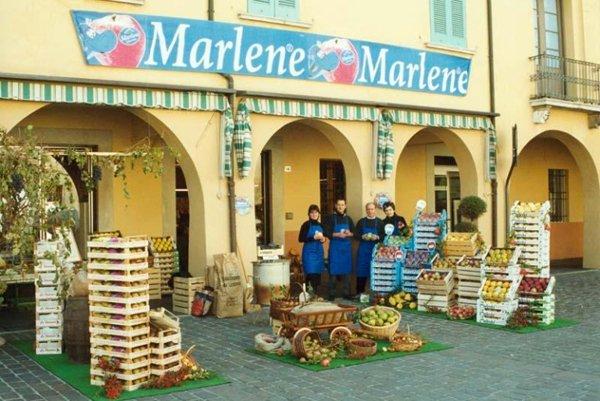 personale vicino a casse di mele e sotto l`insegna della marca Marlene