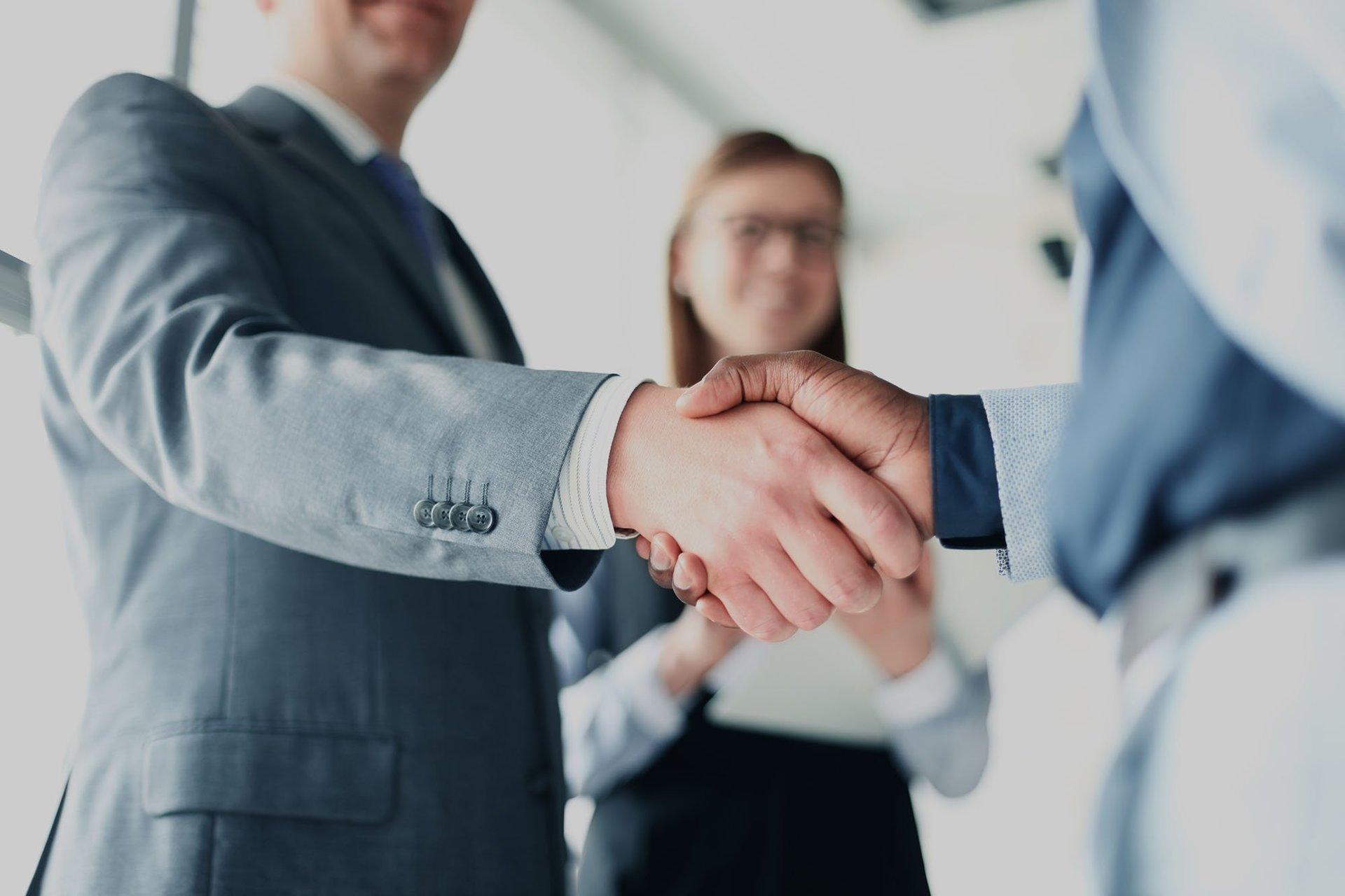 Due signori mentre si stringono la mano e sullo sfondo una donna