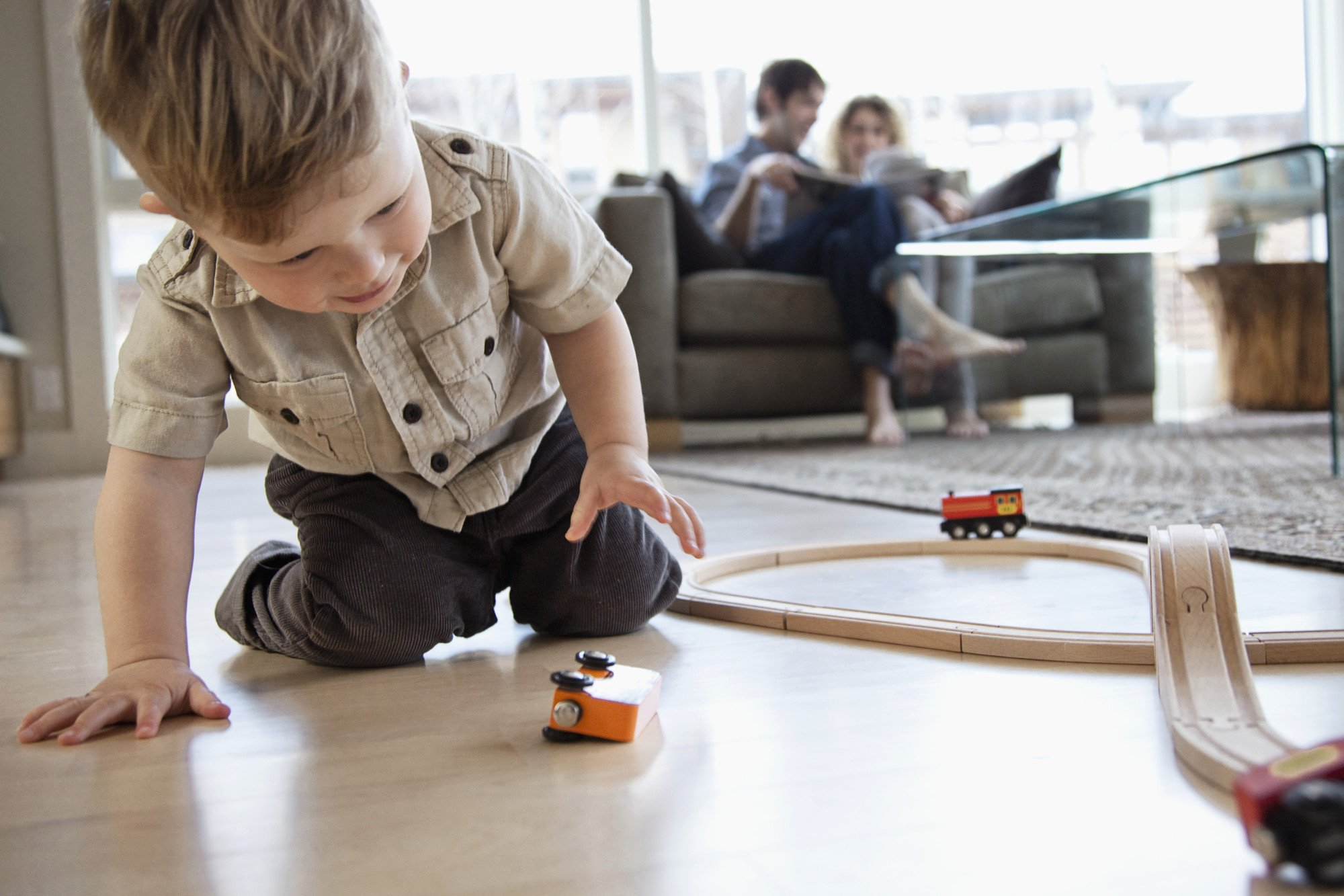 Boy playing on the floor with toy train