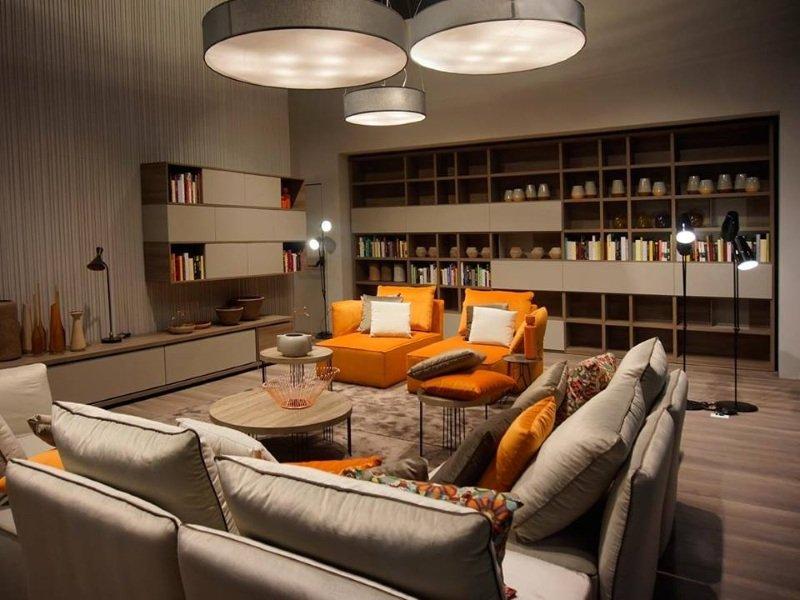 Comfortable e spaziosa camera  in vari legni, una parete questa occupata da una grande libreria. Sofe in grigio e arancio. Moderna lampadina di tre piatti