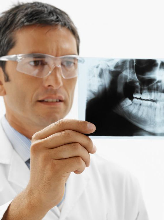 Dentist examining an x-ray to provide good oral hygiene in Anchorage, AK
