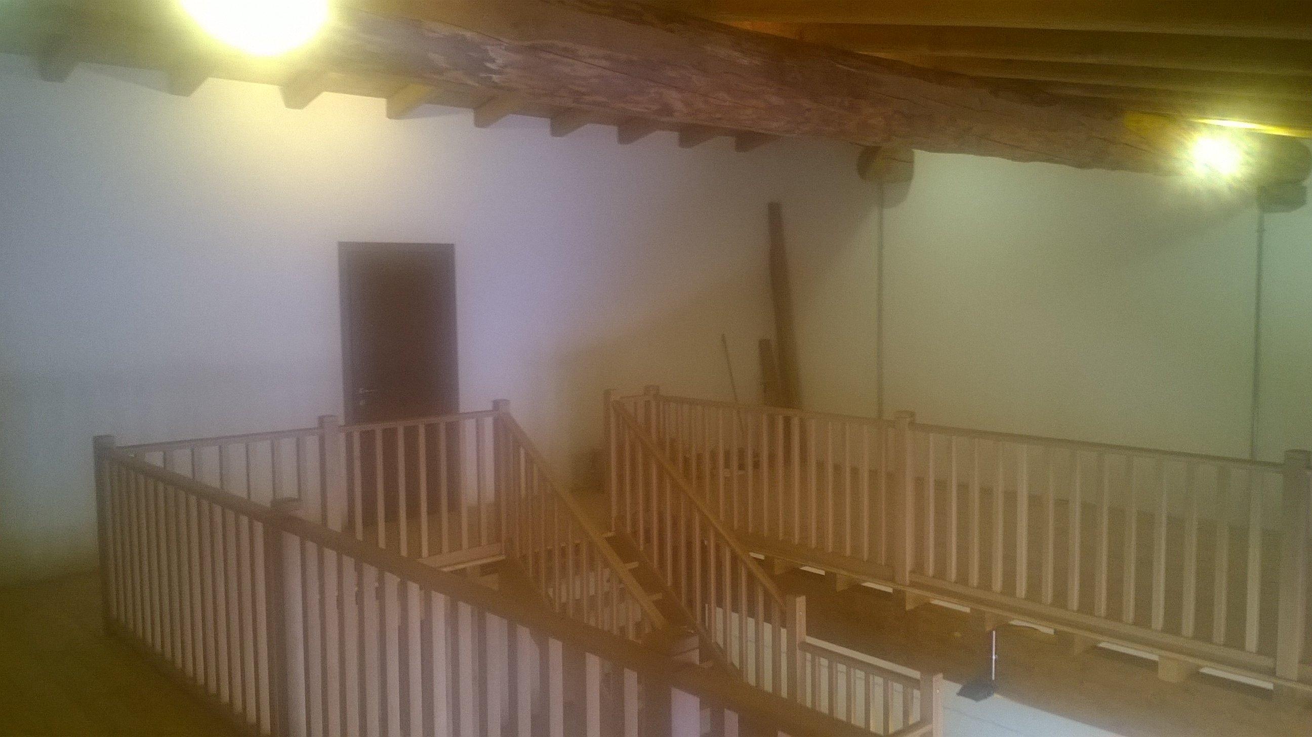 Ringhiera di scalinata in legno con travi in legno a vista