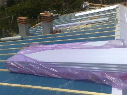 un tetto di una casa con delle assi bianche dentro a un sacco di plastica viola