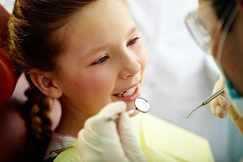 Dentista che esamina la bocca di una bambina