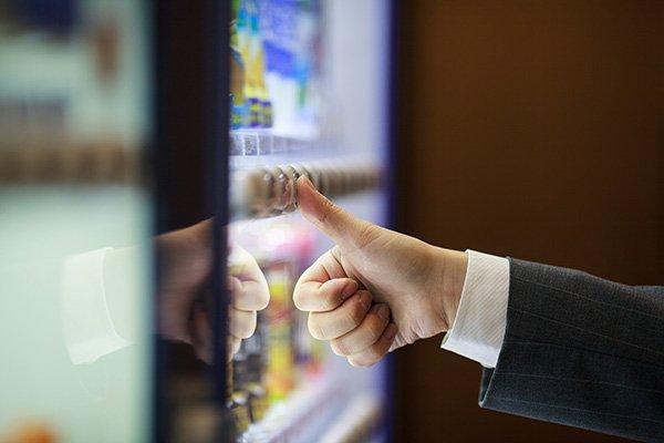 uomo che schiaccia un pulsante per ritirare delle merendine da un distributore automatico